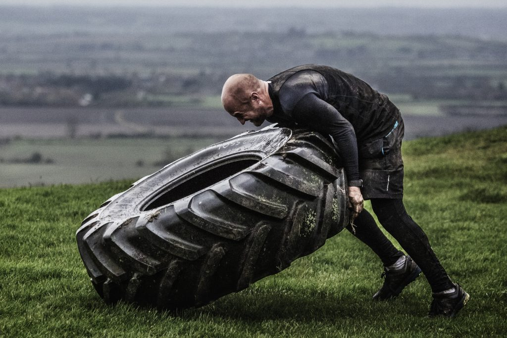 Man lifting a tractor tyre, fitness training.
