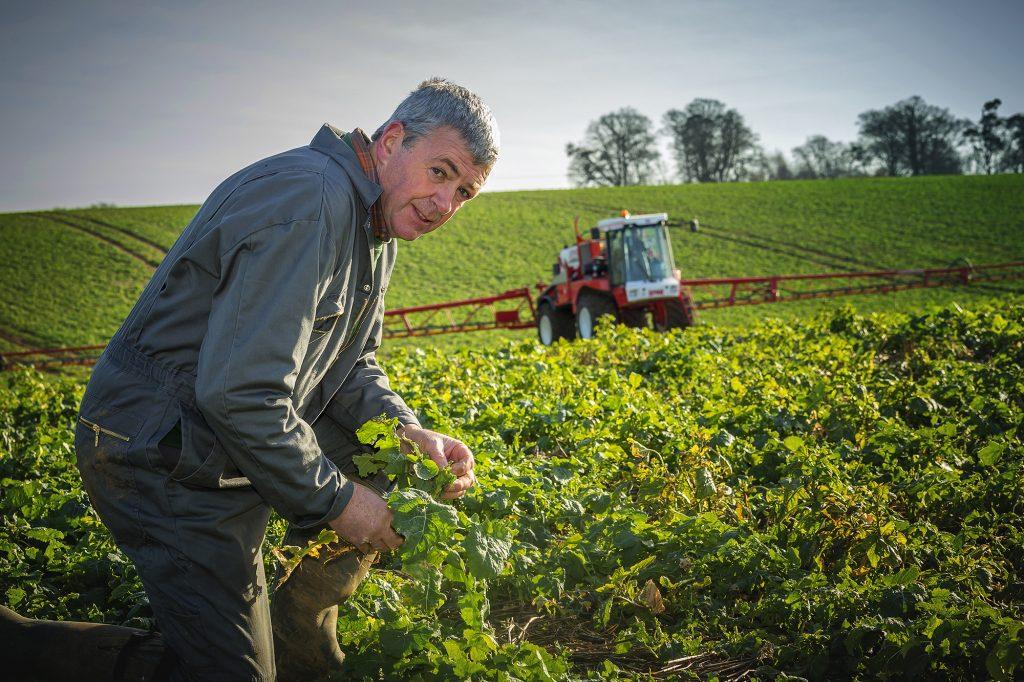 Farmer picking crop in front of crop sprayer